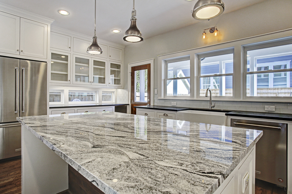 Luxury Kitchen Island with Marble Countertops and Industrial Light Fixtures