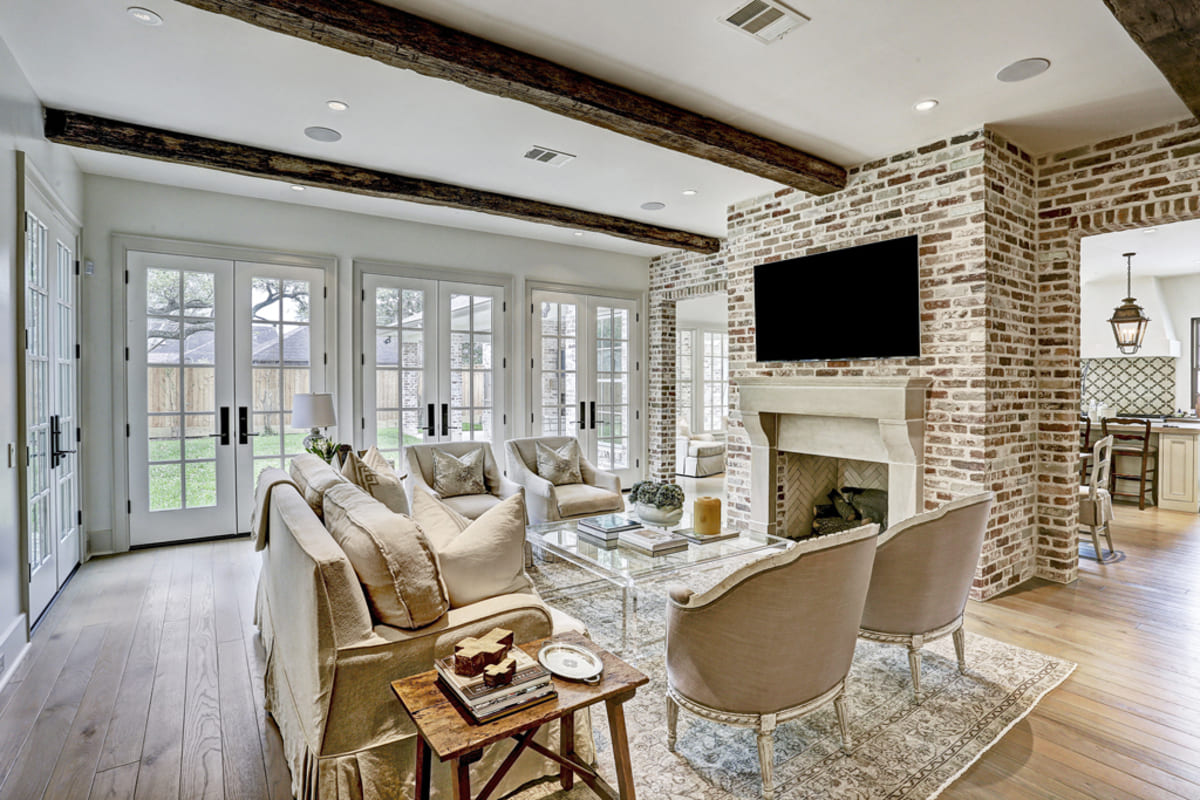 Living area with exposed wood beams and a custom stone mantle on the fireplace