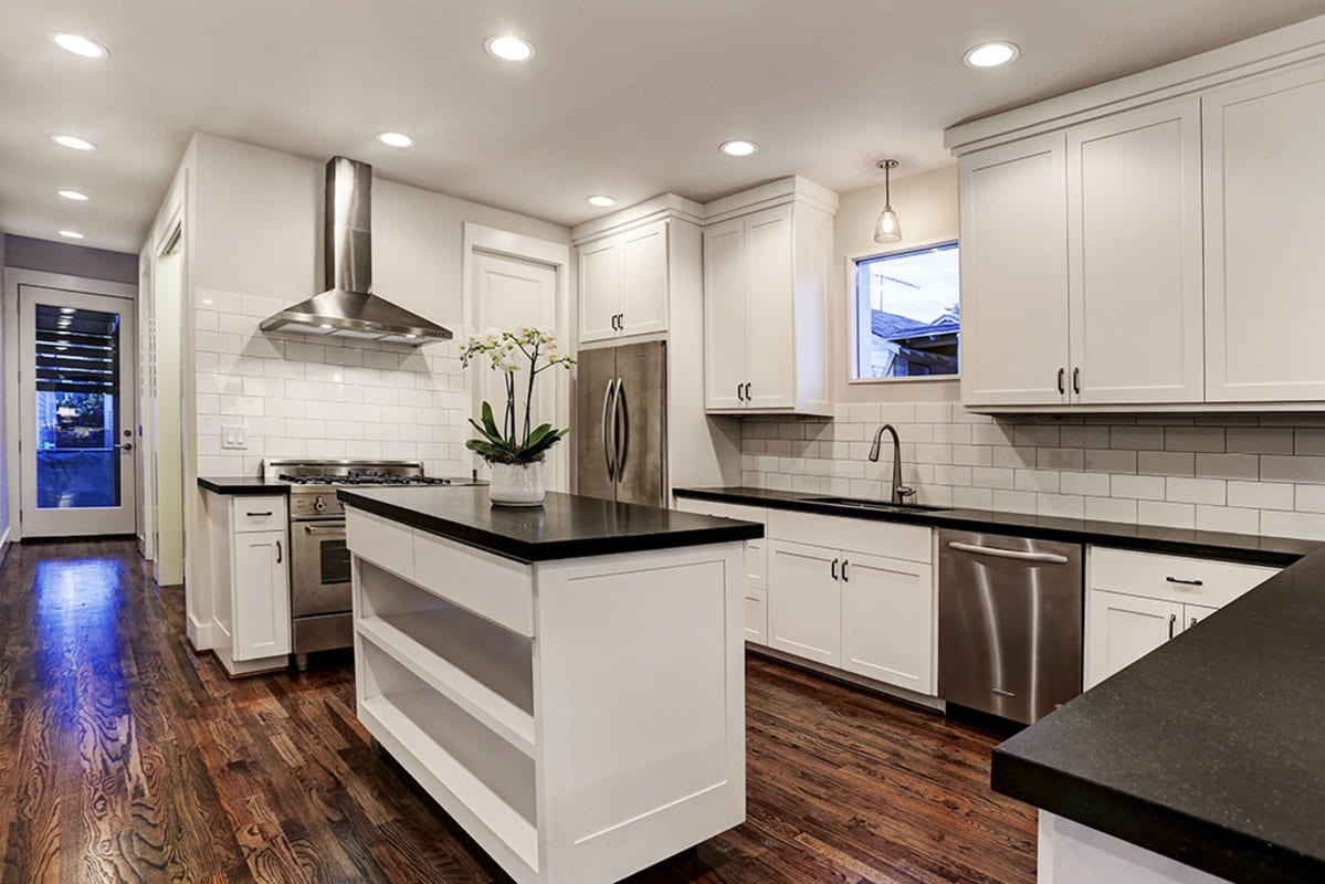 A Modern Farmhouse Kitchen With Black Countertops, White Cabinets, And A Custom Kitchen Island