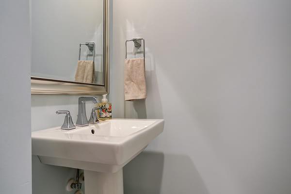 Custom Bathroom With A White Pedestal Sink and A Single Towel Rack
