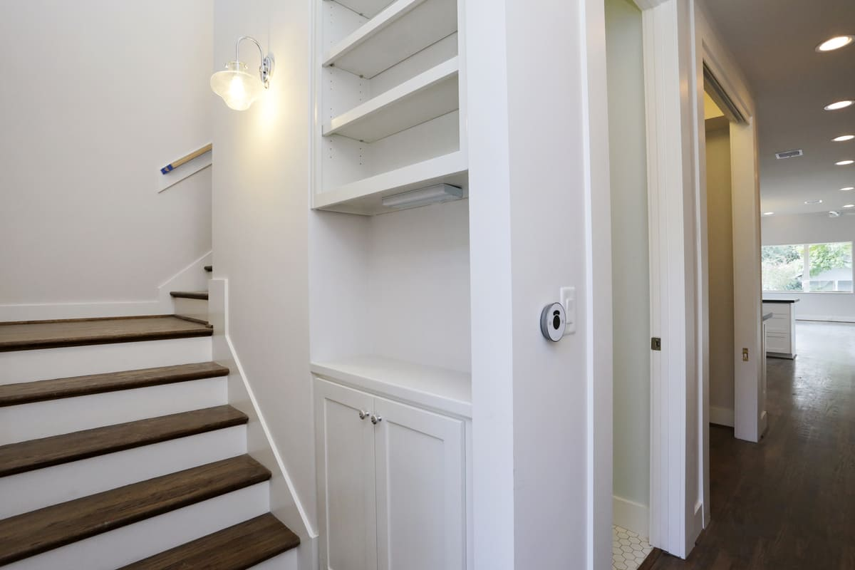 Custom Built Storage Space and Shelves Alongside A Staircase