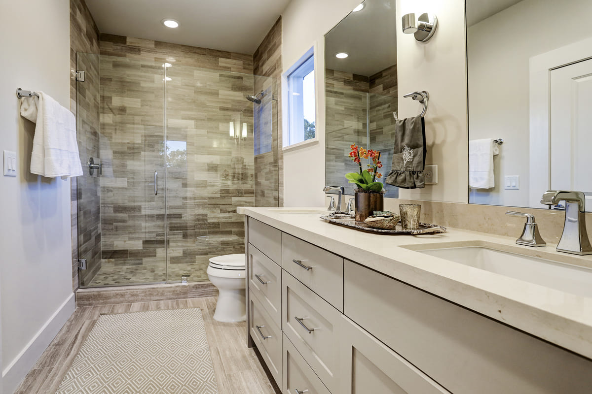 Custom Farmhouse Bathroom With A Walk In Shower, Double Vanity, And Grey Under Sink Storage Cabinets