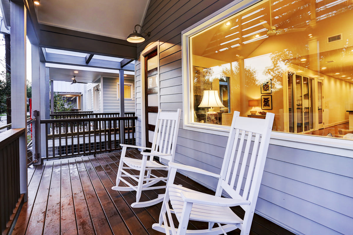 Custom Farmhouse Patio With Two White Patio Chairs, A Large  Energy Sufficient Window, & Light Blue Siding