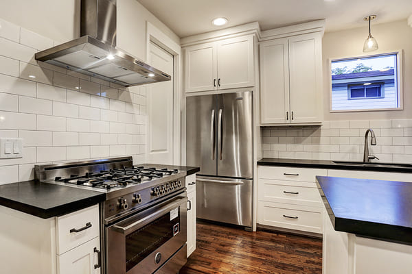 Custom Home Kitchen With Dark Wooden Floors And A Stainless Steal Refrigerator