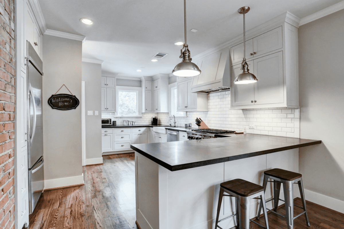 A Custom Home Kitchen with Two Bar Stools and Overhead Lighting in Houston, TX