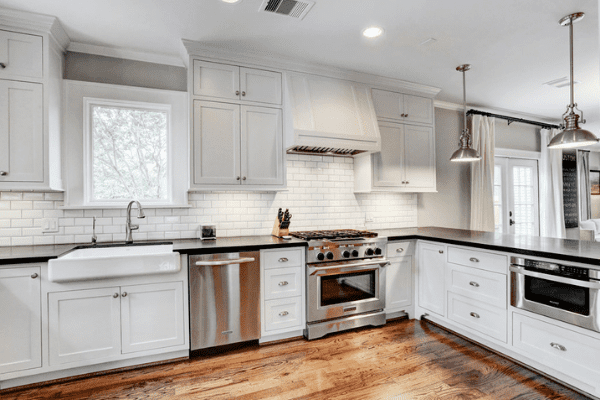 A Custom Kitchen with Wooden Floors, White Cabinets, and Black Countertops in Houston Heights