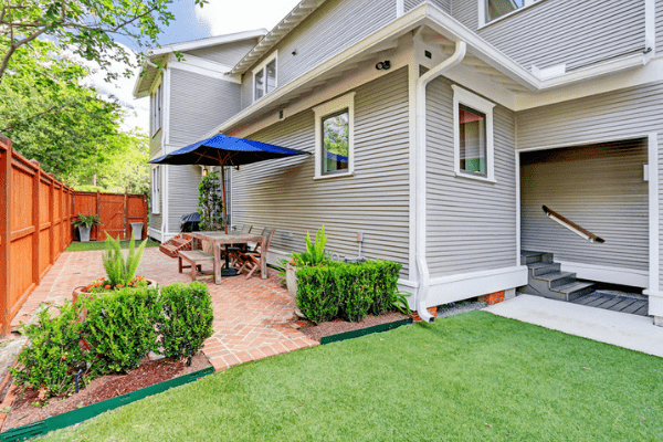 Custom Luxury Home Backyard with Green Grass and a Brick Deck in Houston Heights