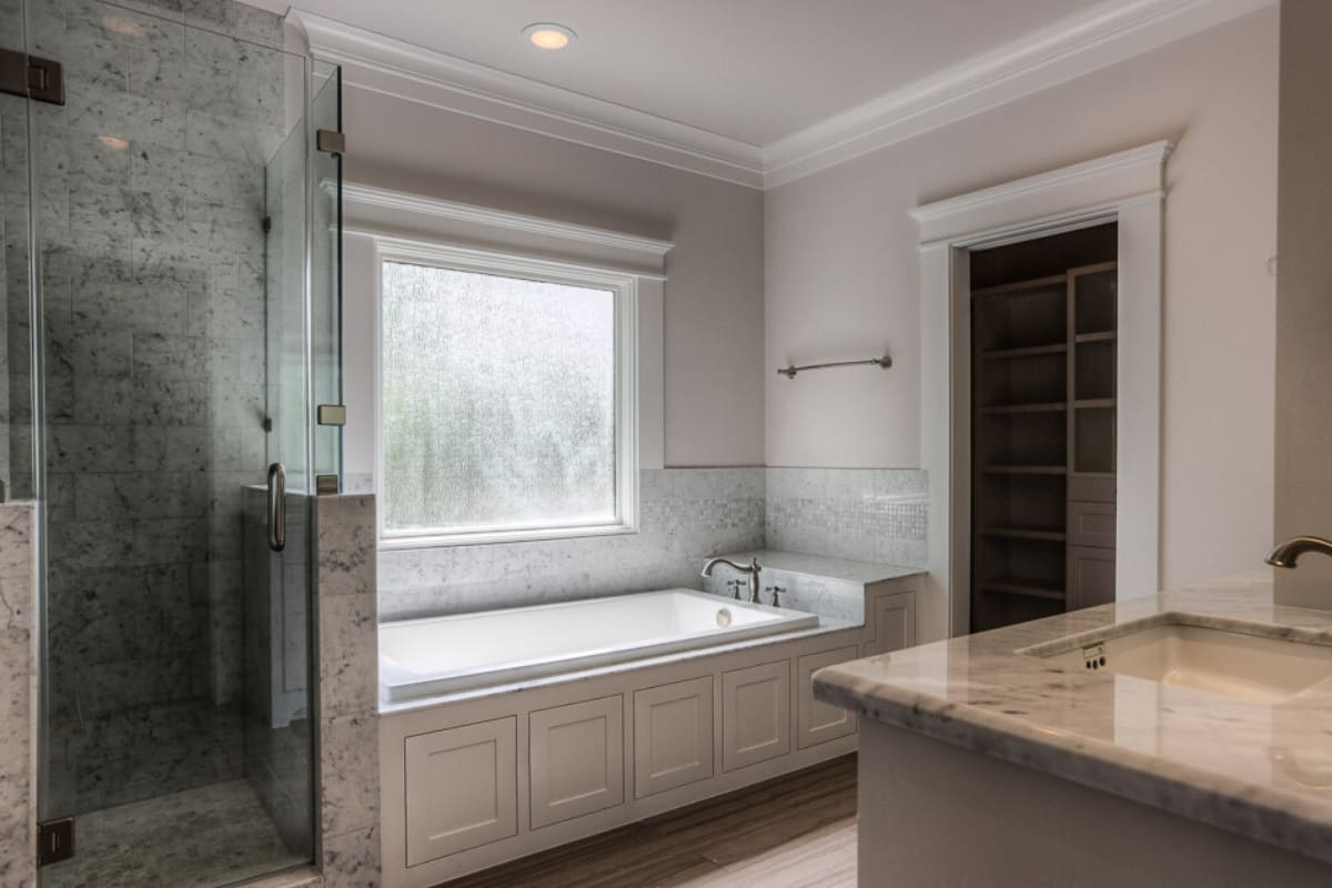 Custom bathtub with built-in storage in Houston bathroom by Southern Green