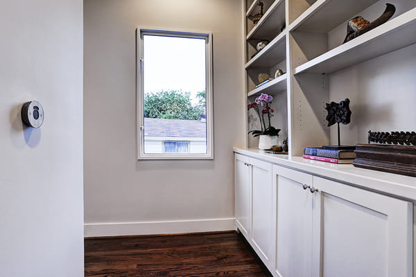 Custom Built White Cupboard Stoarge Space and Shelves Overlooking Upstairs Window